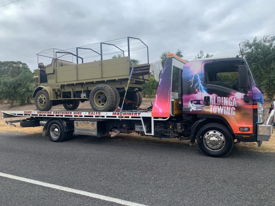Tilt truck towing an ex army vehicle