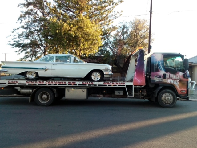 Tilt truck towing a classic American Car which is being towed for restoration