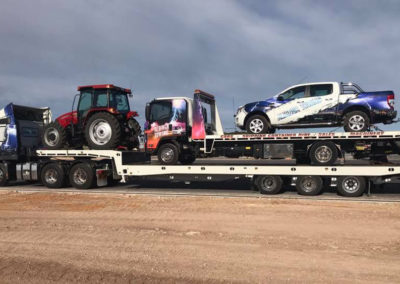 One of the biggest heavy haulage tow trucks transporting a tractor, truck and a car