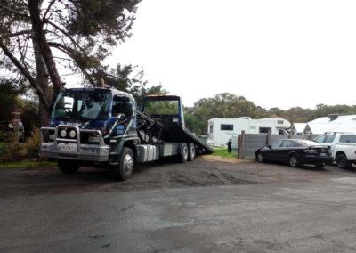 A large tilt tray tow truck unloading  a caravan
