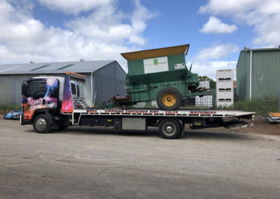 A Tow truck towing a piece of agricultural machinery