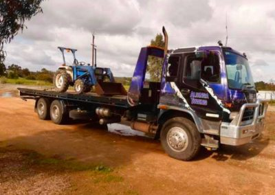 A Tandem Tilt Tray Tow Truck carrying a front end loader in McLaren Vale