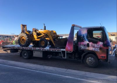 A large tilt tray truck transporting a front end loader in Adelaide